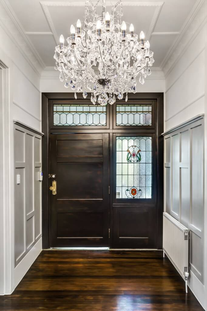 Pale paneled walls and a stunning crystal chandelier balance the dappled tones of the beautiful wood flooring and the deep wood of the front door. Gorgeous stained glass windows stand sentry around the broad front door.