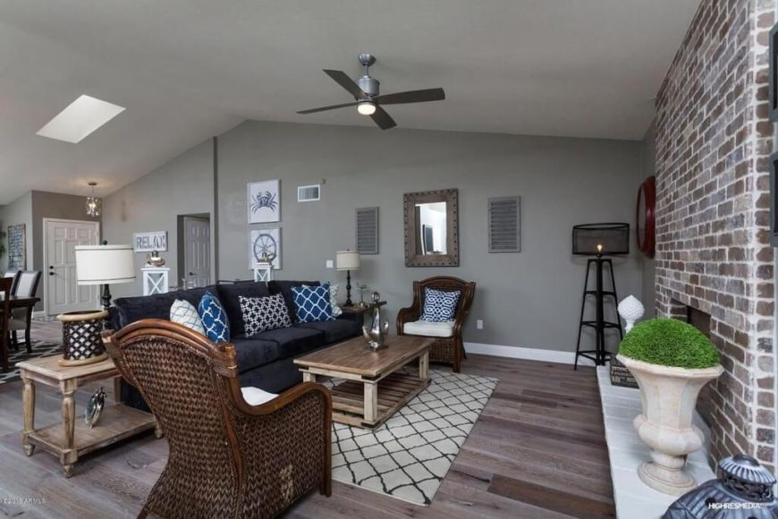 This brushed nickel ceiling fan complements the colors scheme and decor of this room nicely. It also adds to the rugged, industrial feel given to the room but the brick accent wall, natural wood floor, and black floor lamp.