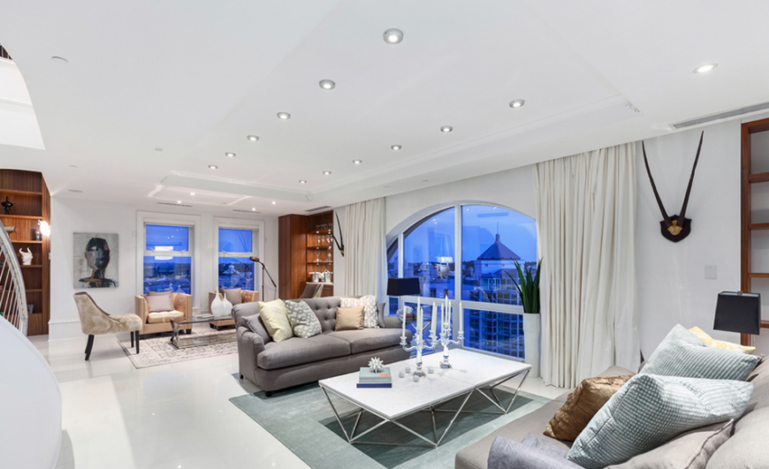 This dazzling living room offers up plenty of light and striking views of the surrounding city, mountains, and ocean. The pale blue and golden accents are reminiscent of the sky at daybreak.