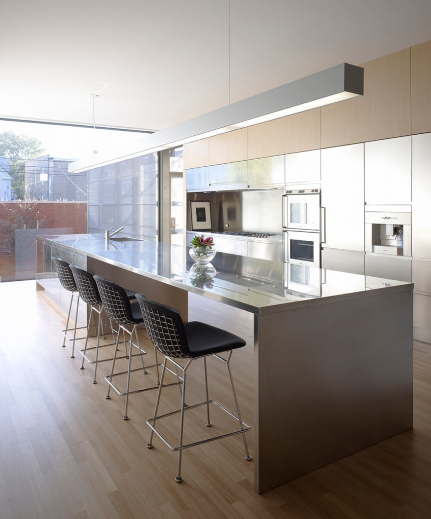 The kitchen is a broad, open stretch of natural hardwood flooring and stainless steel, with an island big enough to house cooking and dining space. Metallic cabinetry helps set the high contrast tone.
