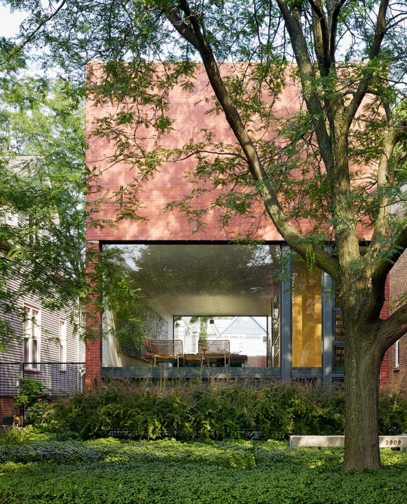 Returning to the front of the home, we can appreciate the vibrant mixture of greens, red brick, and massive stretches of glass in the daytime. The interior and even back yard are clearly visible through the large aperture.
