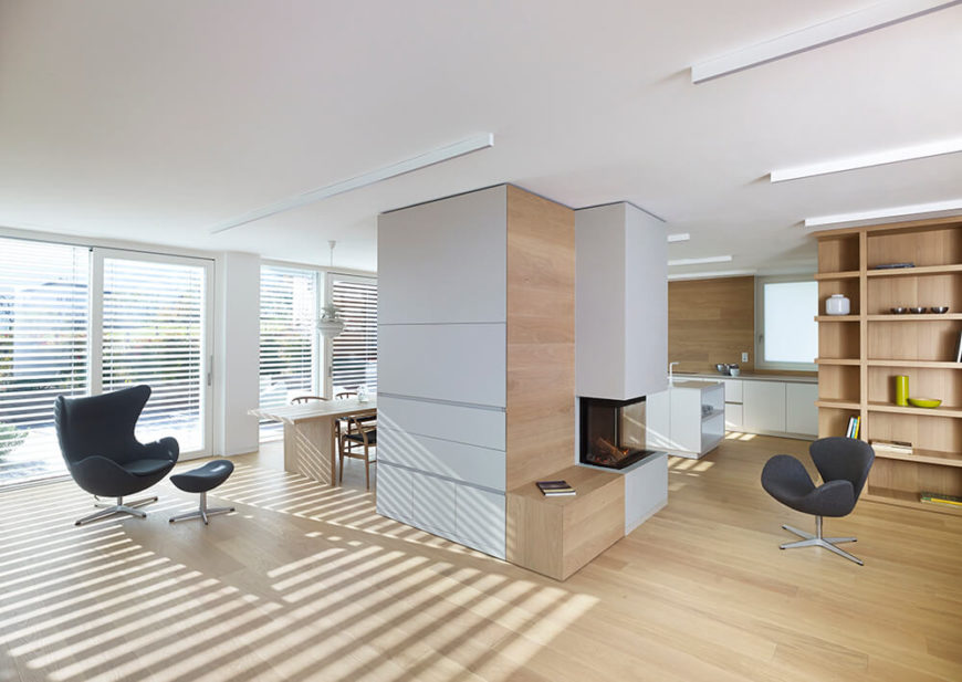 As we move around the pillar to the left, we see a single butterfly chair near the end of the dining table. The whole of the ground floor is covered in windows and glass doors, allowing plenty of light into the home, and warmth in the winter. Lighting consists of long bars along the ceiling, sticking with the minimalist theme.