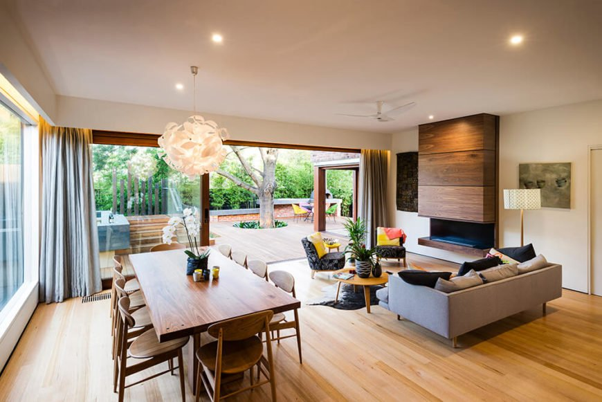 Moving into the home itself, we see the open plan living room basking in the splendor of natural sunlight, through massive sliding glass panels. The interior balances white walls against rich natural wood throughout.
