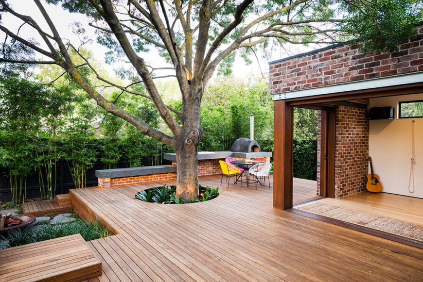 The deck floats gently above the landscape itself, protecting the tree roots which sprawl across the ground. With broad glass sliding panels, the interior flooring appears to transcend indoor/outdoor boundaries.