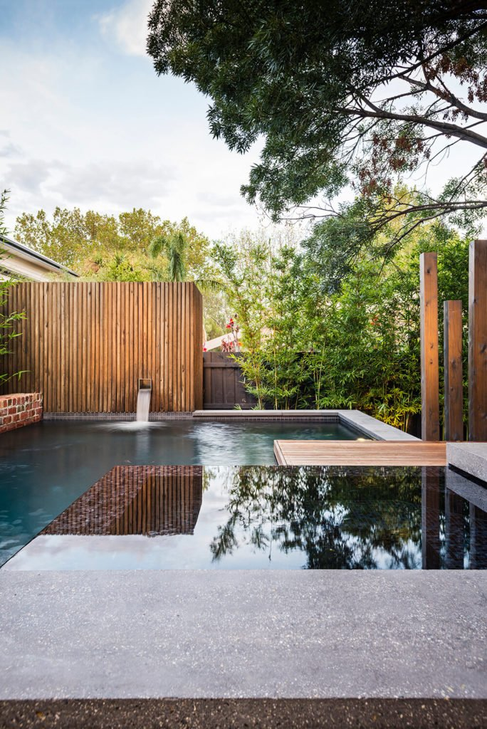 The pool features a built-in jacuzzi, framed by an underwater dividing wall. Here we can see, along with the bamboo covering the traditional fencing, a small spout feeding the pool from behind an enclosed wood space.