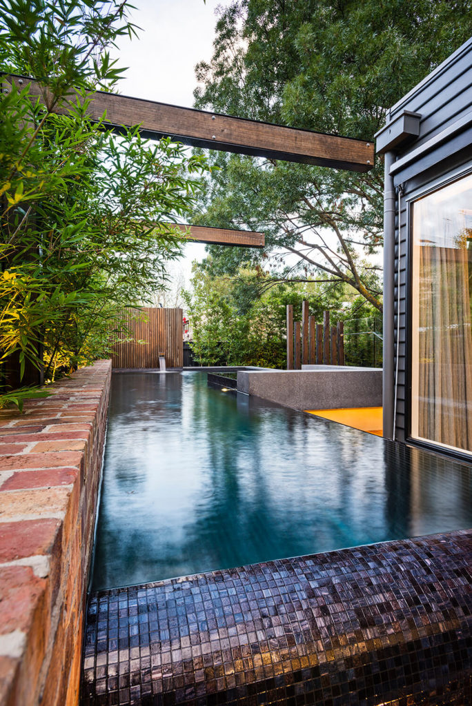 A closer look at the pool reveals the recycled brick edging that supports a row of wraparound bamboo plants in lieu of a traditional fencing solution. The black steel and timber arbors loom overhead to striking effect.