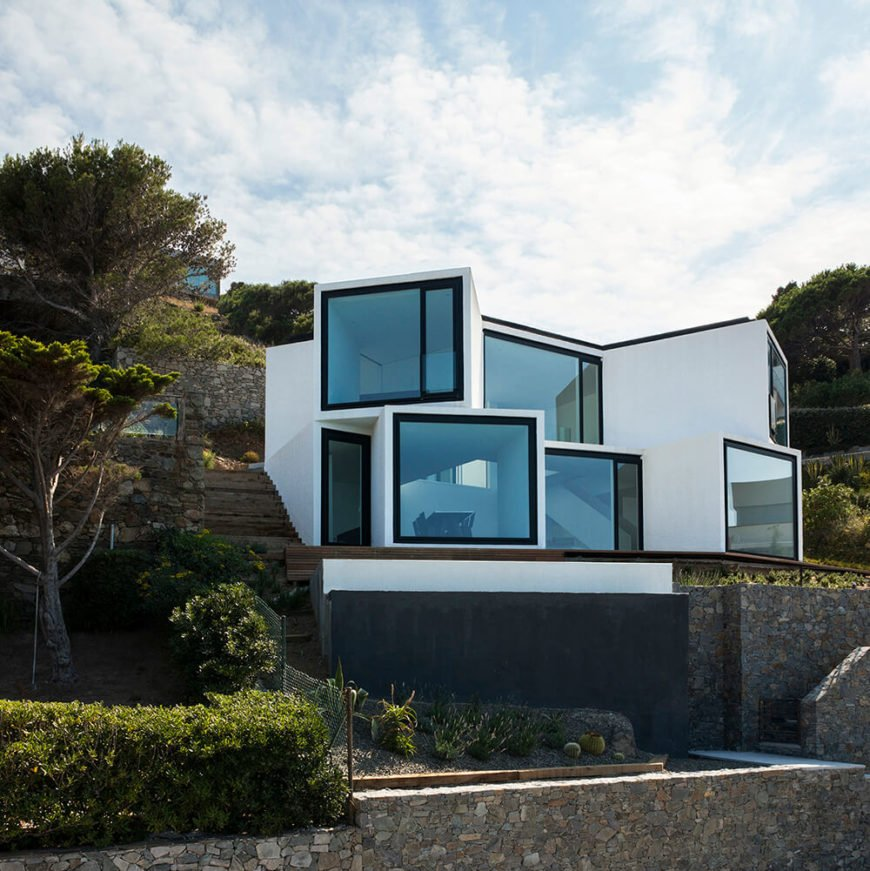 The rear of the home features the most stunning exterior, showing the cube-like structure of the home, with each section punctuated by an enormous panoramic window. The angle of each cube ensures that every window's view is unique.