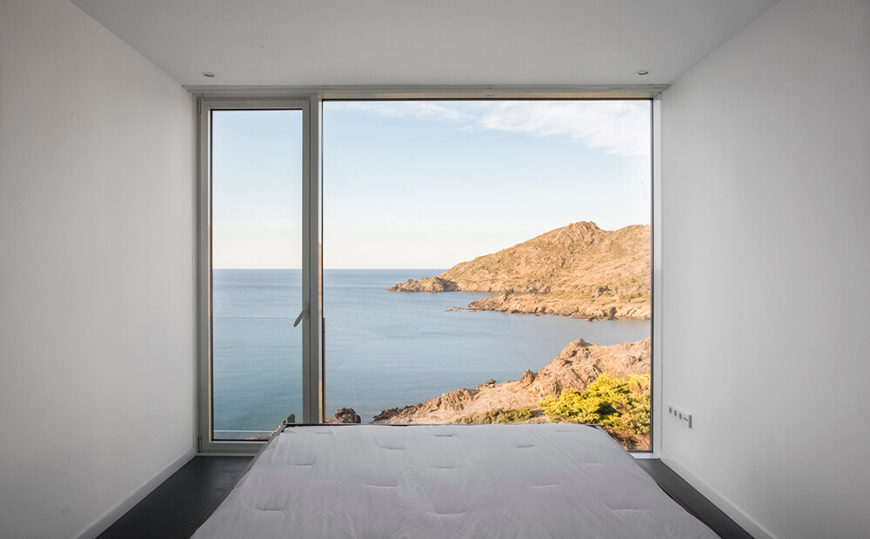 We enter one of the home's minimalist bedrooms, which also features a glass-paneled door that leads outside. Storage is kept behind the bed so that it doesn't obstruct the view of the craggy coast.