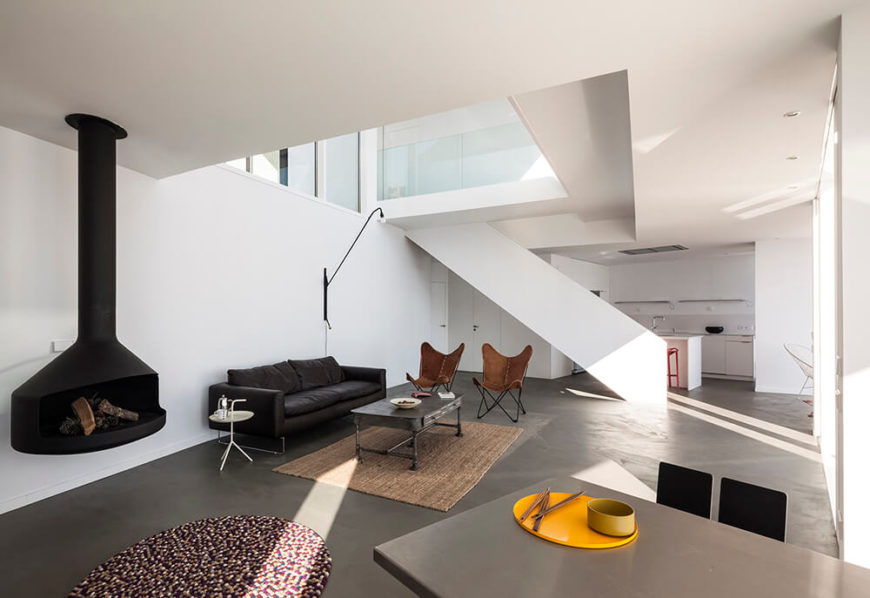 Taking a right off of the stairs leads us into the spacious, minimalist living room, complete with a simple raised wood-burning fireplace. Butterfly chairs and a leather sofa are positioned for an optimal view.