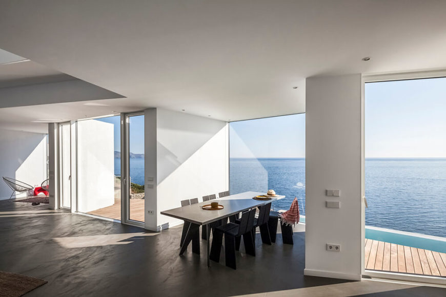 One of the cubes juts out from the main living area and contains a large dining table. The whole of the space is utterly undecorated, allowing the stunning views to take precedent. To the left we can see the sliding glass doors that provide access to the patio and pool area.