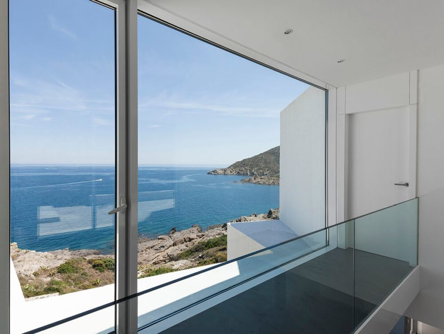 As we move along the hallway, we see a single glass-paneled door that leads out onto the upper terrace of the home.