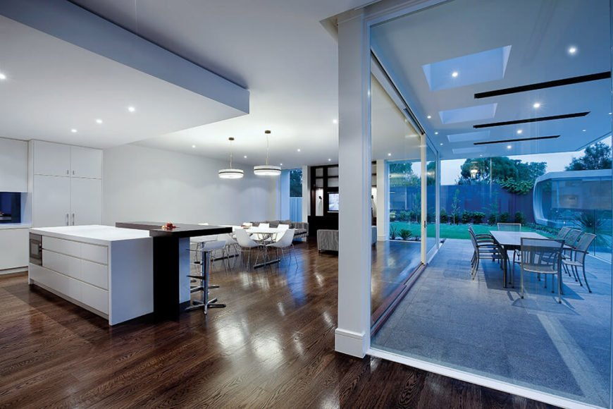 Now we see the kitchen at dusk, with a glow from inside, as well as from the recessed lighting in the patio overhang, spreading across the landscape. The constellation of minuscule light sources keeps the area bright without obstructing the clean lines.