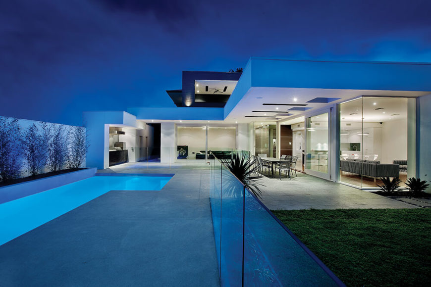 The pool area itself is divided from the lawn and patio by a svelte glass balustrade, allowing for clean and open visual lines across the landscape. The upper floor of the home is visible here, peeking over the wide expanse of patio overhang.