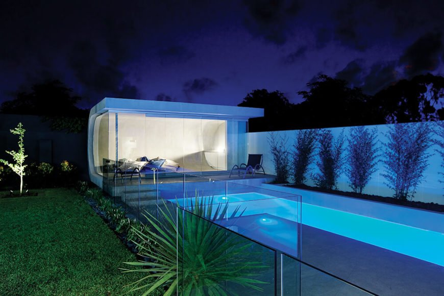 The pool house sits full wrapped within the balustrade, with an interior wrapped in its own seamless glazing. The entire landscape is carefully crafted to emphasize the white toned enclosures and contrast with natural surrounding elements.
