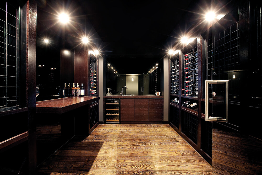 One of the most unique features of this home is a luxurious wine cellar with a built-in bar, wrapped in dark stained wood from top to bottom. With a wet bar and rows of wine racks, this space is fully equipped to store and serve in equal measure.