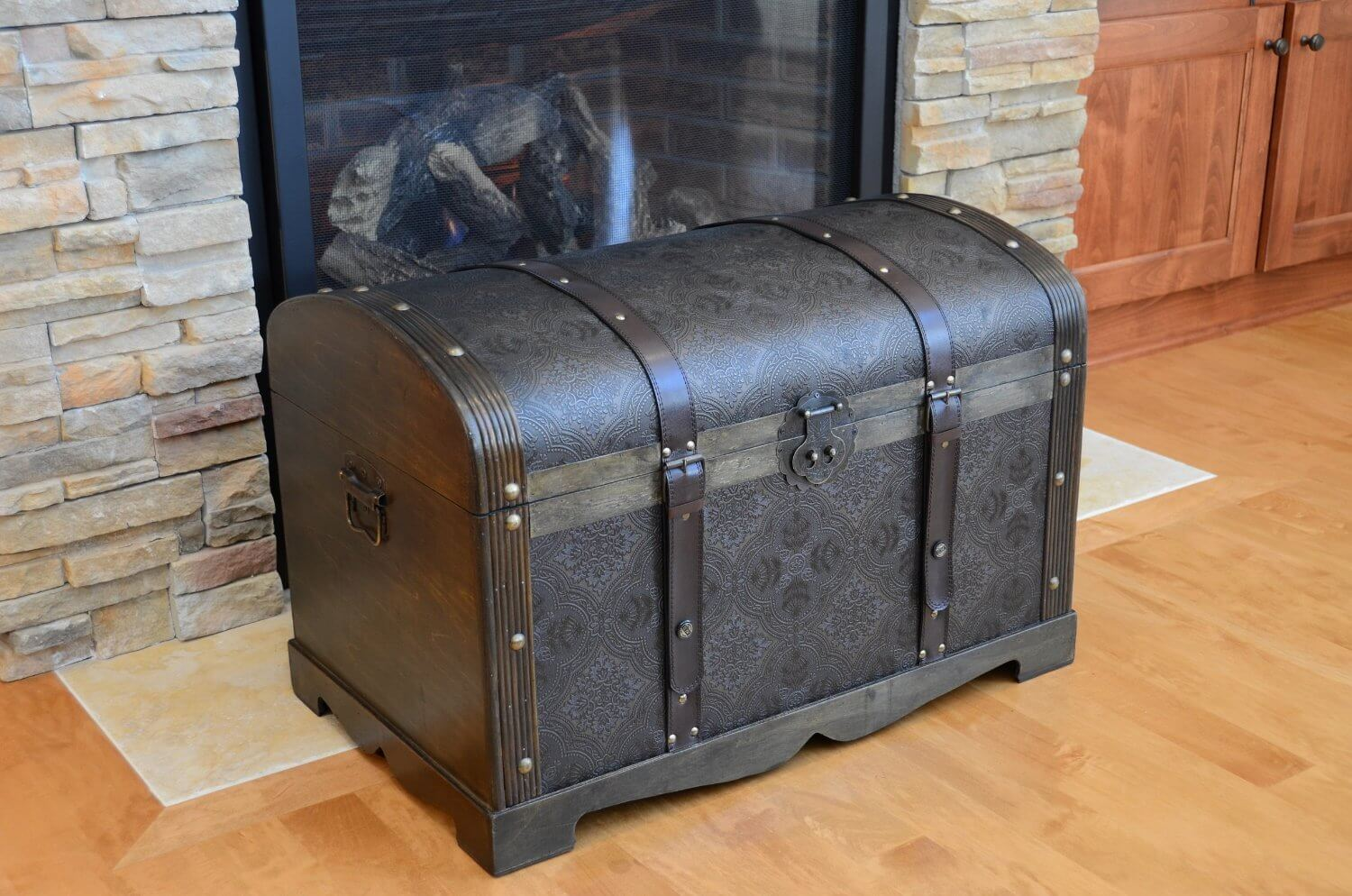 This trunk has a classic curved top with wooden sides and tooled leather. It even includes buckles!