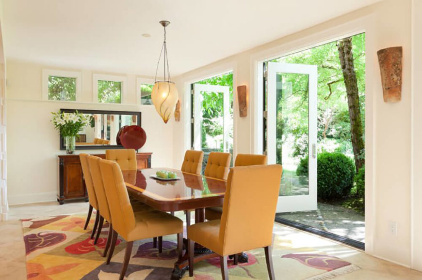 This dining room is bright and airy with white walls and a set of large glass patio doors. The glossy hardwood table is flanked by a set of creamy orange chairs with button tufted upholstery.