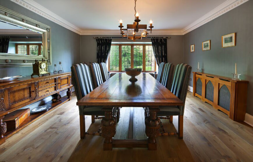 Rustic wood informs the style of this room, with a lengthy decorative side table on each side of the space, and a massive traditional wood dining table at center. The chairs feature striped fabric upholstery over carved wood frames.
