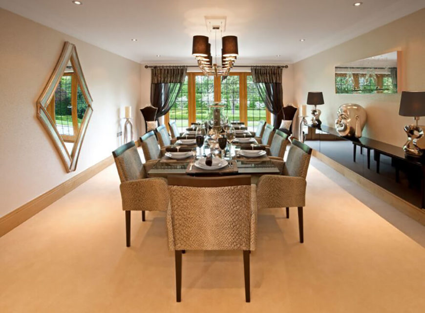 This vast formal din9ing room sees an immense dark wood table running the length of the space, beneath a series of lampshade chandeliers. Intriguing reptile-skin upholstered chairs flank the table.