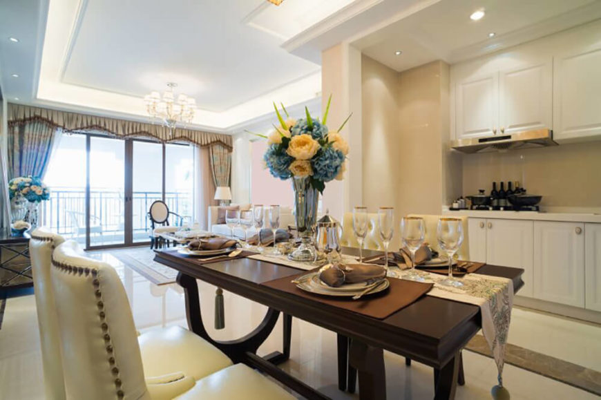 In an expansive dining room spread over white marble flooring, a large dark wood table commands attention at center. Cream toned leather upholstered chairs feature nailhead trim.