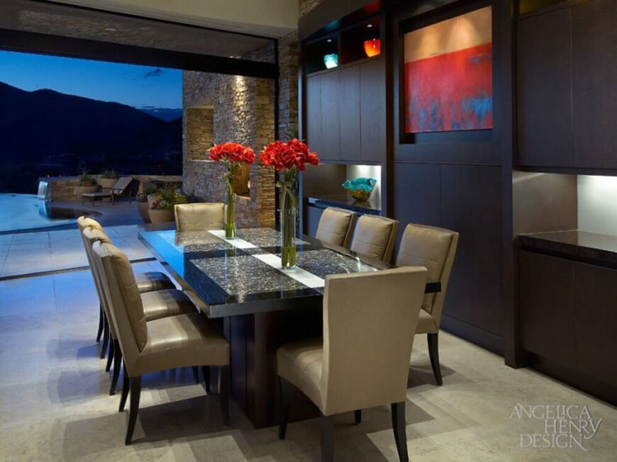 In a thoroughly modern home, deep wood tones mix with stone for an elegant, timeless appeal. The dining table features dark stained wood and granite inlays, surrounded by plush backed leather upholstered chairs.