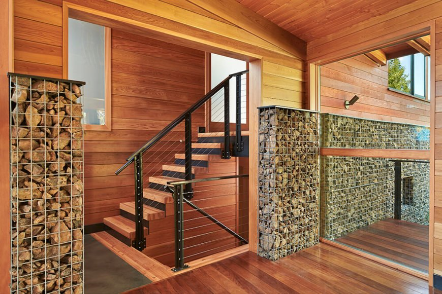 Details such as continuing the use of gabion walls indoors and utilizing sturdy, industrial railings keeps with the rustic, camp feel achieved by the house. This shows off the gorgeous wood paneling and flooring used in the living areas.