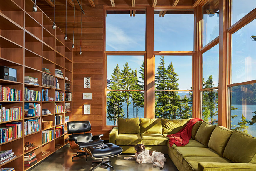 The quiet family room allows access to the view through soaring windows. The comfy velour couch brings the green of the surrounding trees indoors and offers up a nice place to read. Large built-in bookshelves give plenty of storage options.