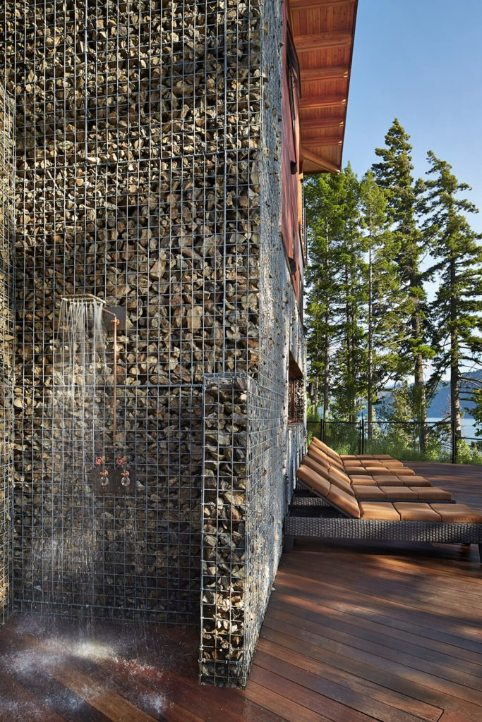 Here is an excellent view of the gabion walls surrounding the outside of the house as well as the simple but striking outdoor shower by the pool.