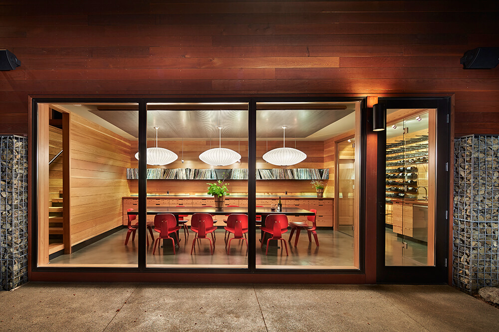 Warm dining room surrounded by shiplap walls and accented by vibrant red chairs. It has a lengthy dining table lighted by large pendants. There's also a wine cellar enclosed with glass walls next to it.