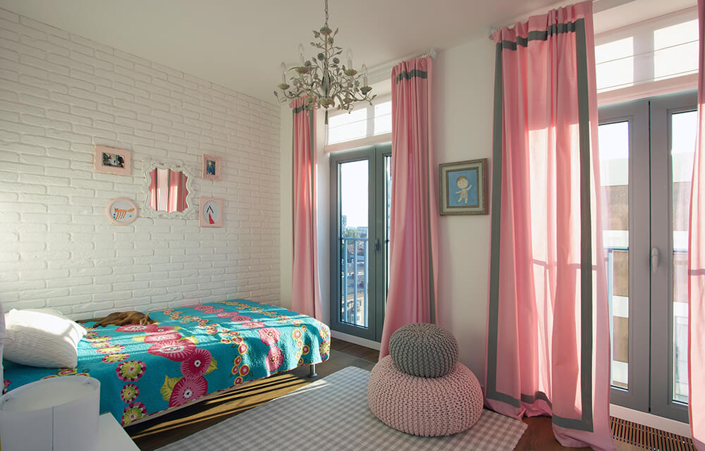 The room also contains two woven bean bags and an elegant floral chandelier. Two sets of double doors lead out onto the terrace and connect the space to the main living area.