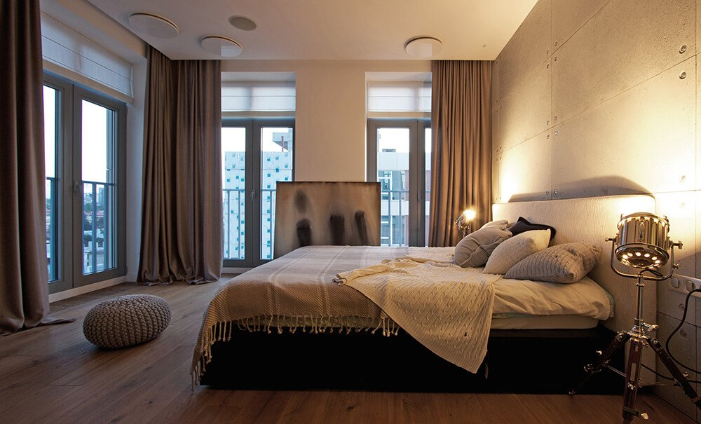 We move back into the primary bedroom, showing the full size of the room. Heavy drapes can be used to block all light coming in through the windows at night, and a soft woven pouf is a nod to the child's room across the hall.