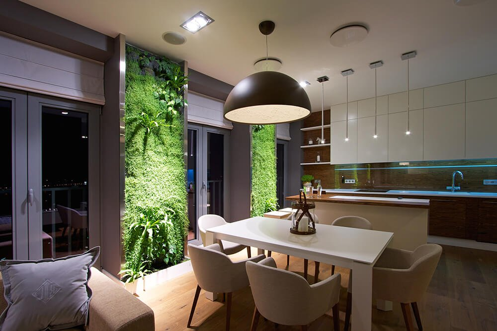 An oversized pendant lamp lit this small dining space. It has hardwood flooring and vertical garden panels that add tropical vibes to the area.