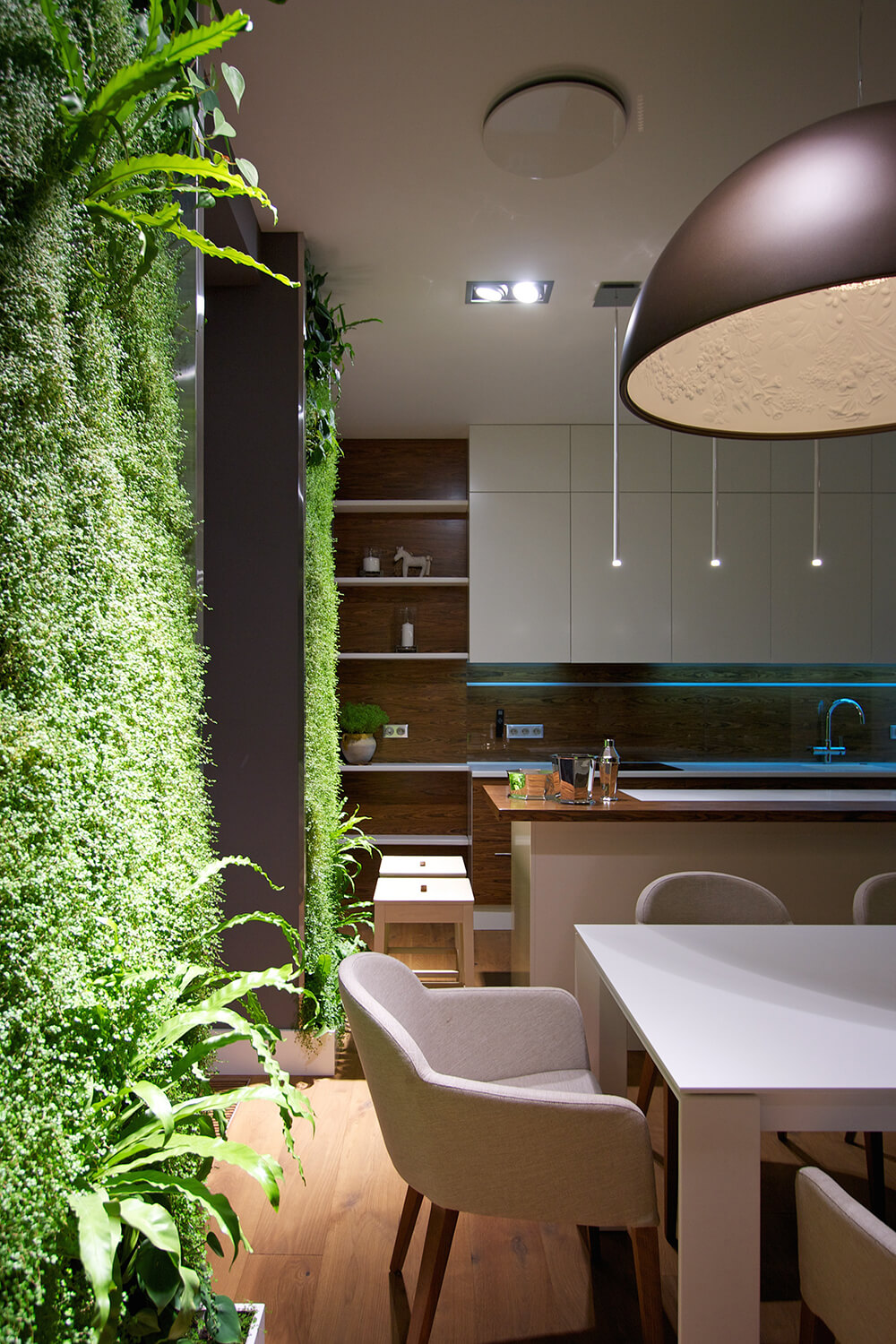 This angle allows us to see the open shelving on the side of the cabinets, along with several small stools. We can also admire the immense texture the green walls add to the room.