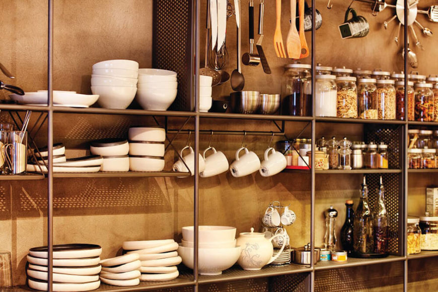 The storage grid becomes easy access kitchen shelving within this area, hosting a series of shelves, hangers, and assorted compartments. This simple industrial element offers both meticulously matched style and function.