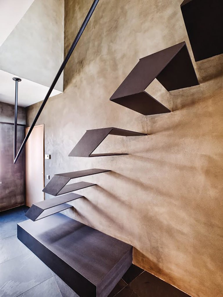 You might have noticed this in the background. The staircase is indeed an intricate set of floating metal platforms, paired with a unique ceiling-mounted hand rail.