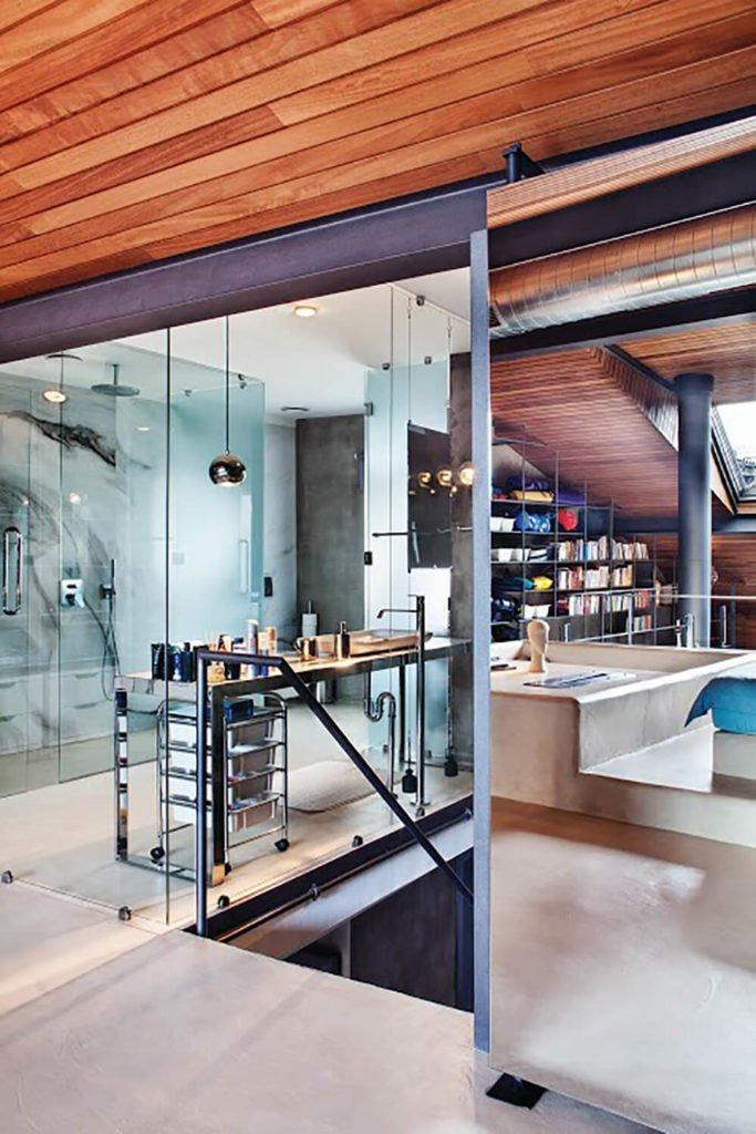 Sliding mirrored panels separate the bedroom from the primary bathroom and staircase. Large glass panels frame the entire space for a uniquely transparent look.
