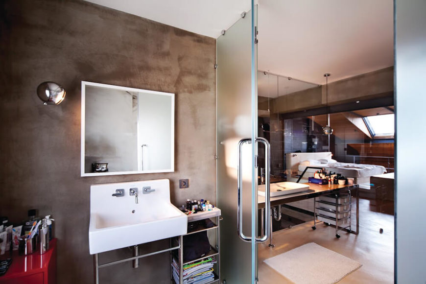 From inside the broader bathroom area, a more private space is available behind smoked glass. A simple pedestal sink setup fits well with the industrial look of the home.