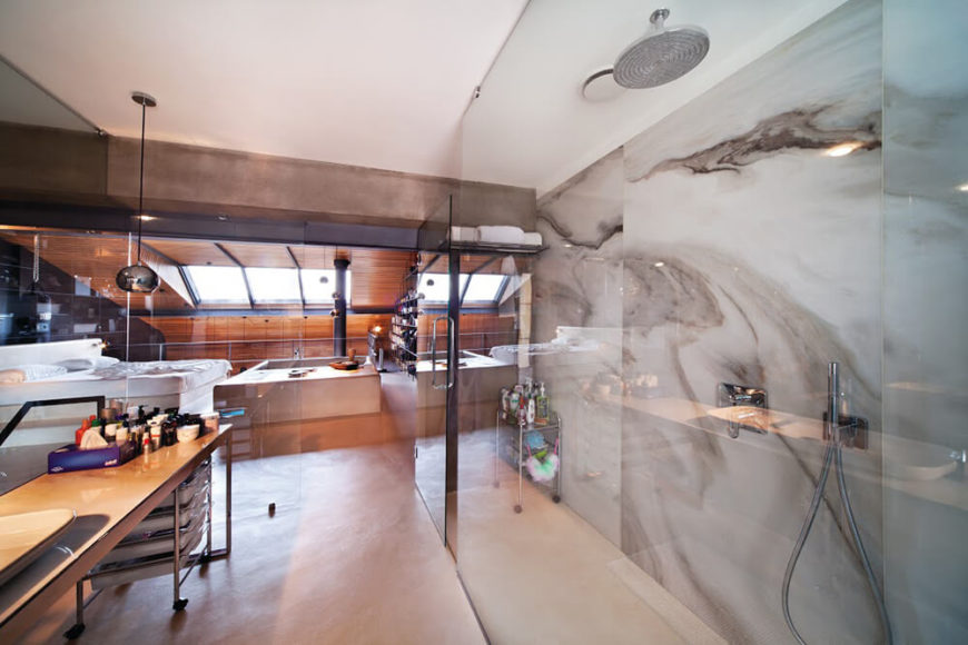The lengthy vanity rests against the glass divide with the staircase, while the massive walk-in shower is backed by more of the marble wall. The entire area is in full view of the bedroom itself.