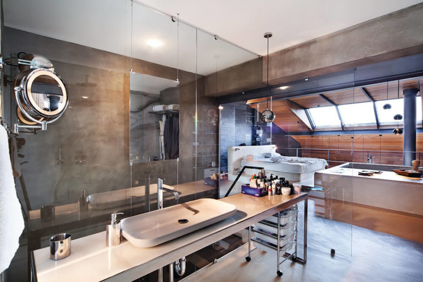 With this closer view we can see the singular mirror mounted on the glass wall overlooking the stairs. A wide vessel sink stands on the metal framed vanity, plumbing fully exposed.