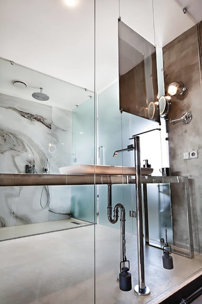 When viewed from the staircase, we can see right through into the bathroom, while the smoked glass doors obscure the more private area of the space.