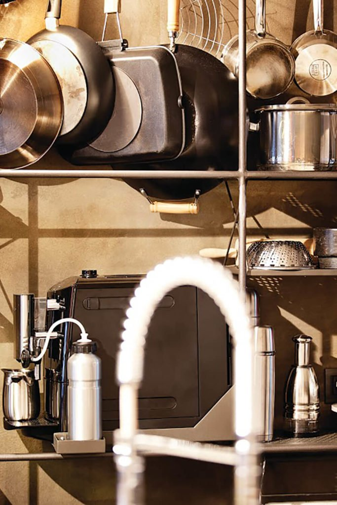 Many of the appliances and kitchen equipment pieces fit into the design theme, with chrome and gunmetal tones.
