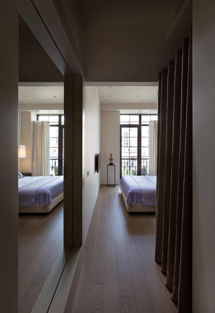 Moving down the hall to the private half of the home, we come to the primary bedroom. This large space is illuminated with sunlight through the glass French balcony doors. The light hardwood flooring from the living room continues uninterrupted here.