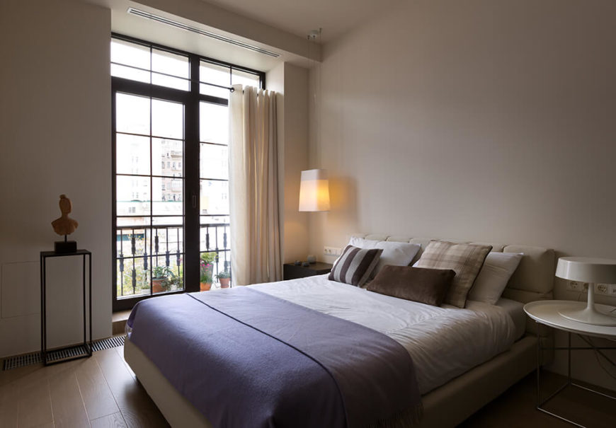 The bedroom features direct balcony access and a minimalist sense of style, with simple light toned walls and a bed set spiked with a periwinkle comforter. A unique hanging lamp floats above the bedside dresser near the balcony.