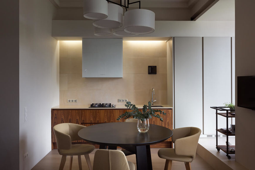 Above the dining table, we see a set of modern barrel lights in white, matching the ceiling tone and full height cabinetry at right. Recessed lighting above the backsplash illuminates the kitchen.