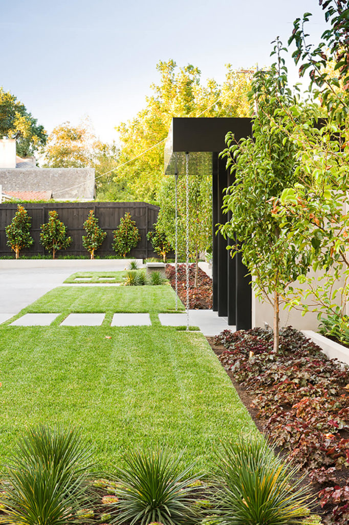 The entry gate, wrapped in black metal and flanked by expanses of manicured lawn, stands apart in stark simplicity. The sharp lines hint at the modern construction home ahead.