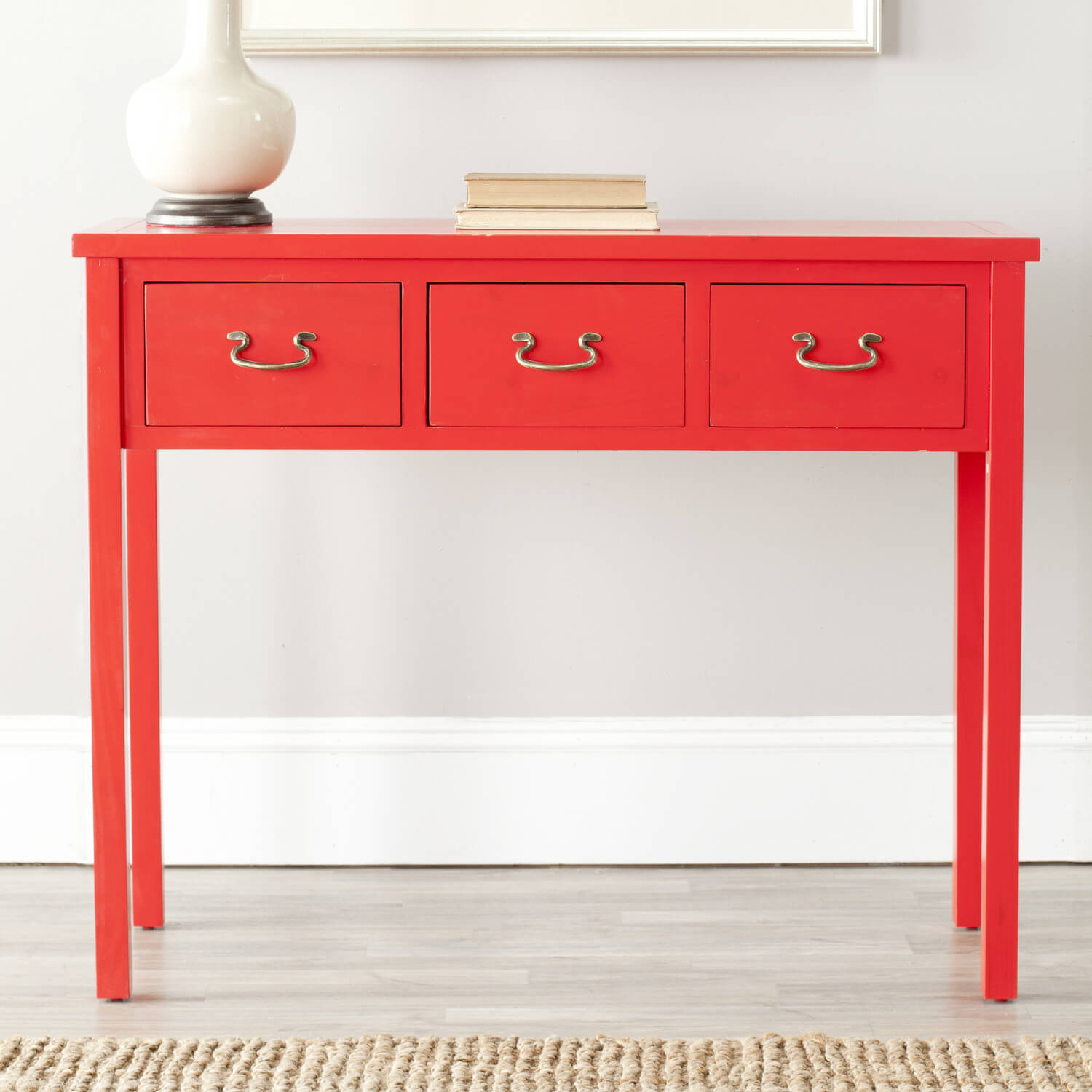 A console table is as at home in the foyer as it is in the living room, featuring three pull out drawers with brass handles and a bright red facade. This table is taller and longer, suitable for a long hallway.