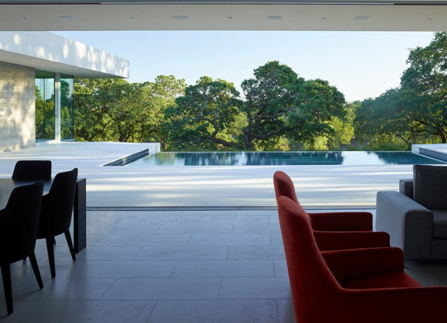 The great room, features a massive 21 foot sliding glass panel, and here we see it fully retracted. This allows for the interior to spill out onto the poolside courtyard, utterly erasing the line between indoors and out.