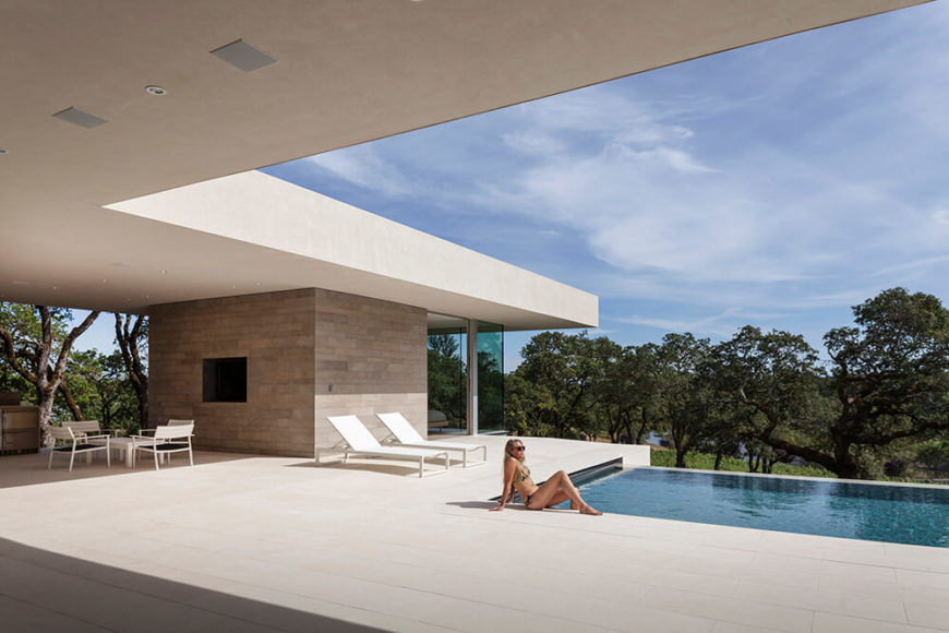 Across the sleek expanse of minimalist concrete, we see the guest house, wrapped in 270 degrees of glass and facing the landscape beyond. To the left is the sheltered outdoor kitchen area, connecting the two spaces beneath a common roof.