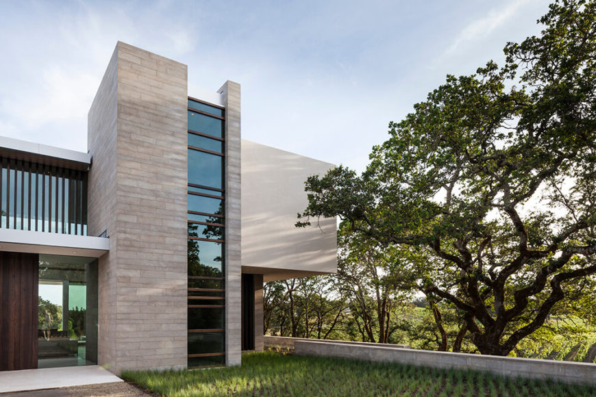 The wood panels help tie the home's modern construction to the land, offering a sense of warmth amidst the expanses of concrete and glass. They also afford it some necessary privacy.