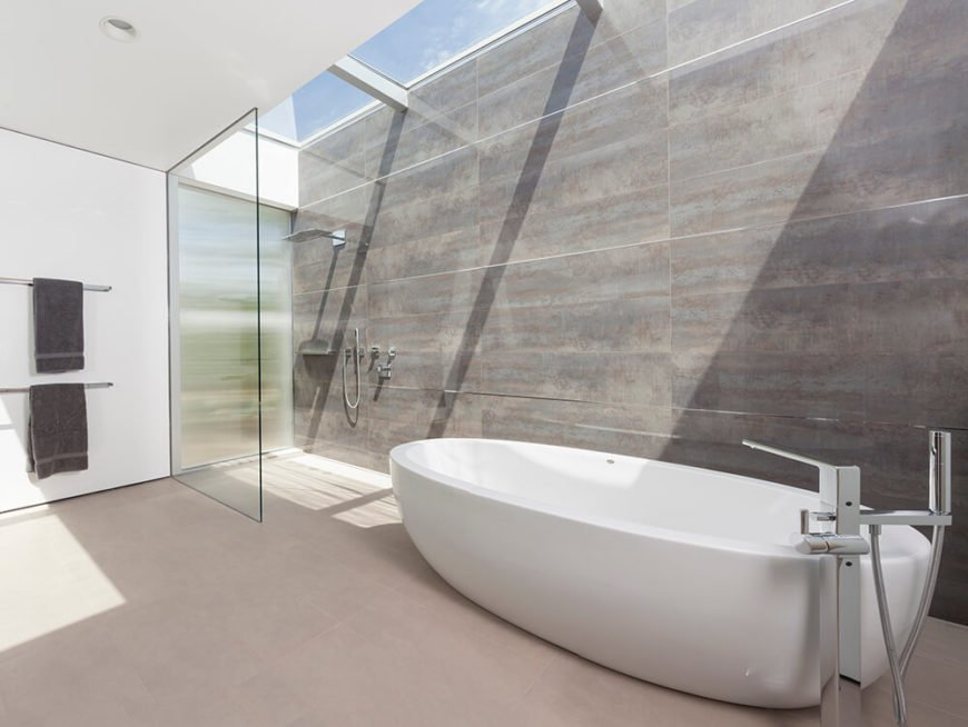 The primary bath is an immense minimalist space, filled with concrete, glass, and white walls. A room-length set of skylights ensures natural light in daytime, glowing over the walk-in shower and large white pedestal tub.